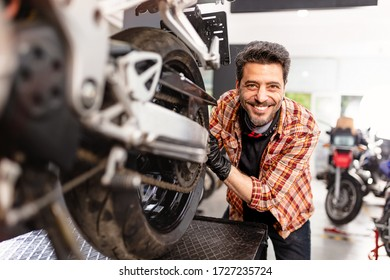 Motorbike repairman working in shop.