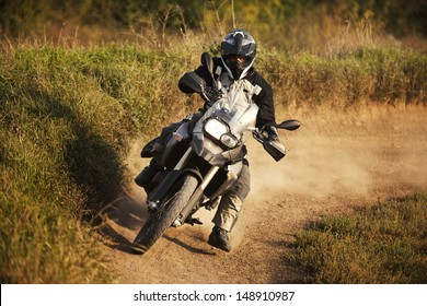 Motorbike rider on track. Strong grain added to create atmosphere, outdoor shot.