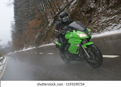 Motorbike riding in very bad and snowy weather on a road in the three land point of Belgium, the Netherlands and Germany, Eifel/ Belgium - March 24 - 2009