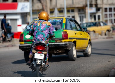 Motorbike in traffic of Cotonou, Benin. The people of Benin in daily life, lifestyle of West Africa. Fashion of Benin, West-Africa.