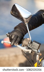 Motorbiker arm in black glove holds twist grip throttle and brake with two fingers, close up view