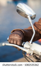 Motorbiker arm in brown leather brown glove holds twist grip throttle, close-up view with mirror