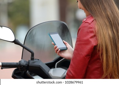 Motorbiker on her motorbike checking smart phone information and showing screen