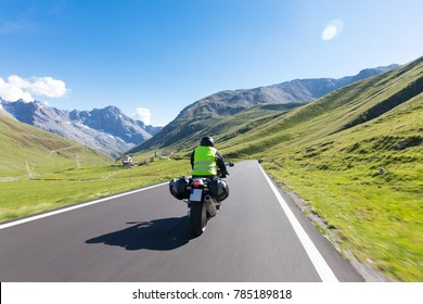 Motorbiker is riding his bike through a beautiful Landscape over winding streets roads through the alps and mountains
