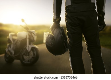 Motorbiker stands in front of his motorcycle