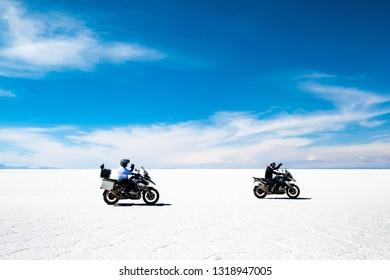 motorbikers and car riding among sunshine Salar de Uyuni