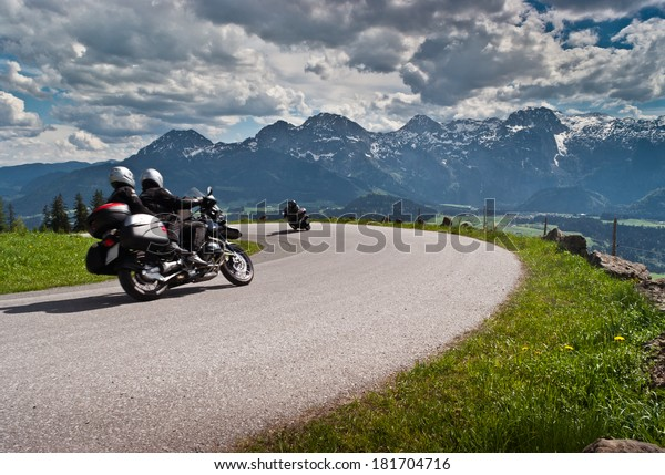Motorbikes on the road in mountains with Alps in background.Salzkammergut,Austria.
