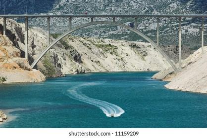 Motorboat in a bay sailing under a big highway bridge, horizontal frame