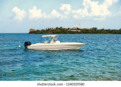 Motorboat or boat at anchor in sea or ocean in Philipsburg, St Maarten at tropical beach on sunny day on blue seascape. Summer vacation, travelling, wanderlust concept