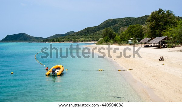 Motorboat docking beside the beach on mountain background