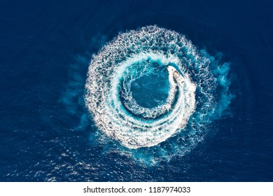 Motorboat forms a circle of waves and bubbles with its engines over the blue sea