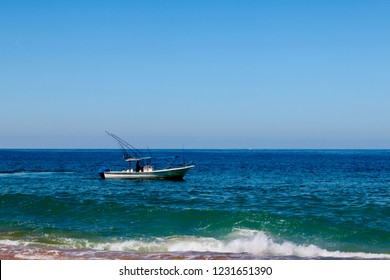 Motorboat idling on the Mexican Pacific coast; beckons the angler for sport, but also shuttles tourists & locals to isolated parts of the Pto. Vallarta shore, and  brings in seafood for market trade.