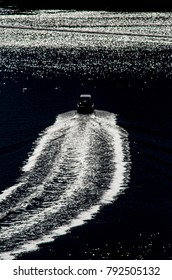 A motorboat leaves a train in the morning waters of the Hawksberry River near Brooklyn New South Wales, Sydney, Australia