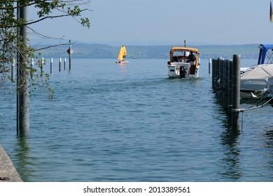 motorboat leaving harbor Altnau. German shore at horizon. lake Bodensee, CH Switzerland. 20th July 2021