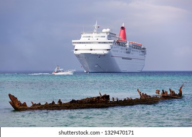 The motorboat passing by between drifting cruise liner and remains of a ship sunken on Seven Mile Beach, Grand Cayman Island (Cayman Islands).