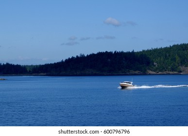 Motorboat raising a small wake on Puget Sound under blue summer skies.