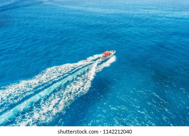 Motorboat at the sea in balearic islands. Aerial view of floating boat with people in transparent blue water at sunny day. Summer landscape. Top view from drone. Seascape with yacht in motion in bay
