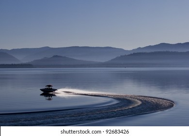 Motor-boat silhouette on lake Tahoe. Evening photograph of California lake with speed boat and foggy mountains on background.