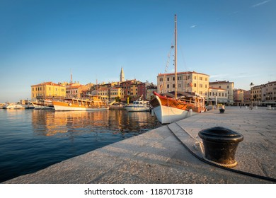 Motorboats and boats on water in port of Rovinj. Medieval vintage houses of old town. Yachts landing, high tower of Church of Saint Euphemia. Morning sunrise blue sky