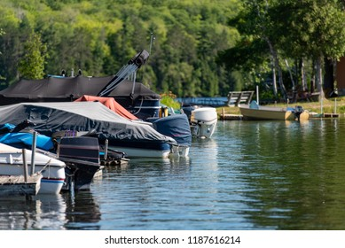 Motorboats docked on a lake in Ontario Canada's Cottage Country on a summer morning.