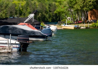 Motorboats docked on a lake in Ontario Canada's Cottage Country on a summer afternoon.