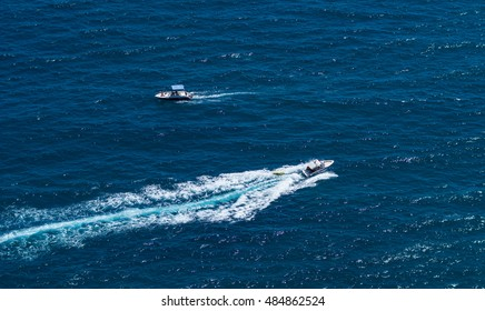 Motorboats on the sea, white foam trail on blue water