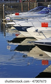 Motorboats and yachts for sale, moored in a marina