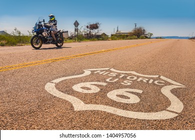 A motorcucle drives by the marker on historic Route 66 in Arizona.