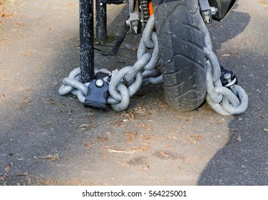 Motorcycle anti-theft chain with padlock security lock on rear wheel, protection against theft