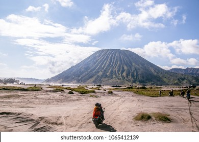 motorcycle bigbike drive to the adventure driving mortocycle into Beautiful active Volcano with smoke Mount Bromo on from Pananjakan Peak at Java island in Indonesia, photo from drone on bird eye view