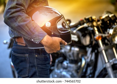 Motorcycle, Biker wear jeans suit hold helmet and retro motorcycle background.