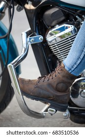 Motorcycle boot on the footboard of a motorcycle, close-up