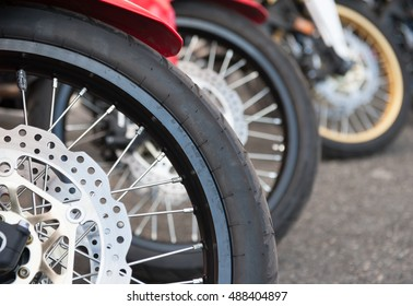 Motorcycle brake and wheel close up, group of wheels out of focus in background