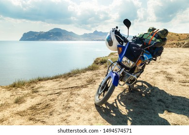 motorcycle with camping equipment on a mountain against the sea