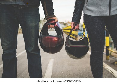 Motorcycle couple holding helmets in hands