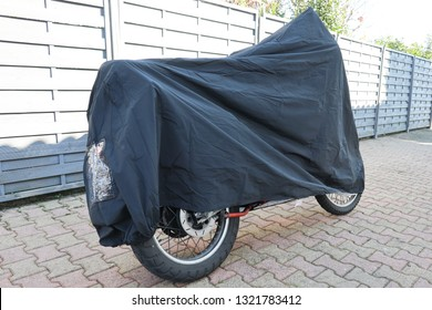 motorcycle covered with grey cover near the wall in the street