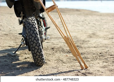 Motorcycle and crutches on the beach