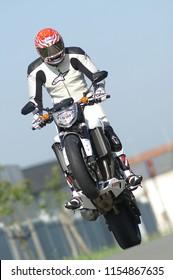 Motorcycle driver doing a standing wheelie on White Yamaha motorbike in Wetteren/Gent/Belgium - September 11 - 2008