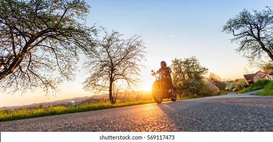 Motorcycle driver driving in beautiful sunset light