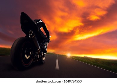 Motorcycle driver is driving on the road in the direction of the sunset