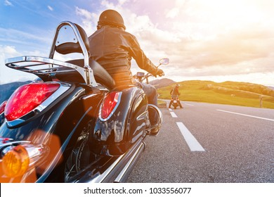 Motorcycle driver riding in Alpine highway, Nockalmstrasse, Austria, central Europe. Nontraditional back side view.