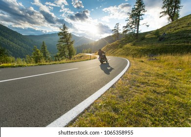 Motorcycle driver riding in Alpine highway, Nockalmstrasse, Austria, central Europe.