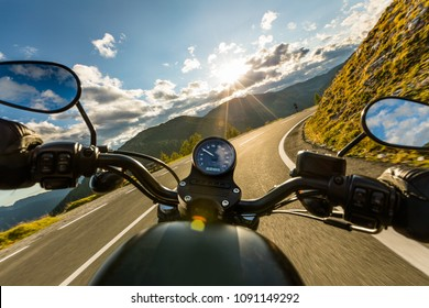 Motorcycle driver riding in Alpine highway, handlebars view, Austria, central Europe.
