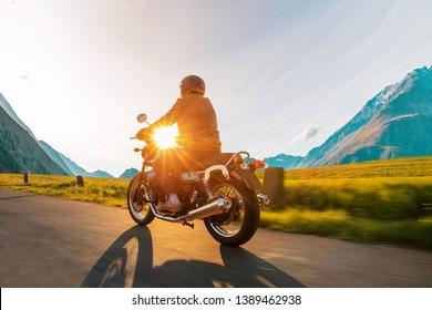 Motorcycle driver riding in Alpine highway, Nockalmstrasse, Austria, central Europe.