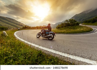 Motorcycle driver riding in Alpine landscape. Lifestyle photo with motion blur effect.