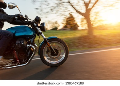 Motorcycle driver riding in European road. Outdoor photography, countryside landscape. Travel and sport photography. Speed and freedom concept