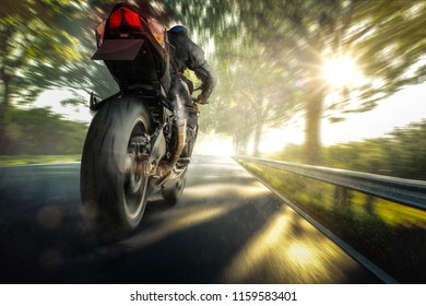 Motorcycle is driving on a country road