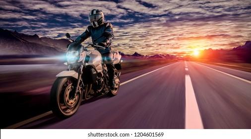 Motorrad fahren bei Sonnenuntergang auf leerer Straße. Abenteuerfreiheit von Einzelfahrern Motorrad auf der Autobahn. Kopienraum für Einzeltext auf der rechten Seite.