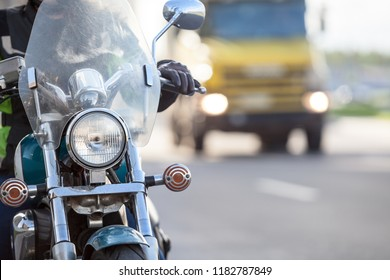 Motorcycle driving without turning on headlight, freight truck behind, urban road