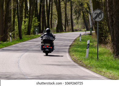 A motorcycle at the end of a road section with speed restriction